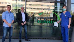 Bernhard Wehrenfennig (r.), von den Hochtaunus-Kliniken erhält von Nils Winkes von der medacom GmbH (l.) und Björn Richter (2.v.l.) von der Stratasys GmbH die ersten Schutzvisiere aus dem 3D-Drucker.