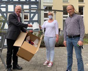 Olaf Gerlach, Geschäftsführer der medacom GmbH, übergibt die ersten 3D-gedruckten Schutzvisiere an Frau Vögele und Herrn Pappert von der Altenhilfe St. Elisabeth in Marburg.