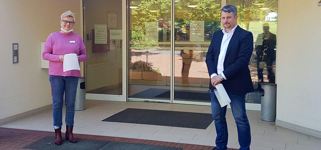 Heimleitung Anja Asmussen und Sales Manager Christian Rosenbecker bei der Übergabe der Gesichtsvisiere an das AWO Sozialzentrum